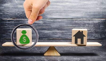 House with money on the scales and wooden blocks. The concept of real estate purchase. Sale of property. Payment of the mortgage. Redemption of taxes. Tax refund. Credit for the apartment. Stock Photo