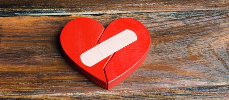 A red heart with a plaster. Renewal of the relationship. Family psychotherapist services. Reconciliation. Saving the family. Search for compromises. Conflict, dispute resolution 写真素材