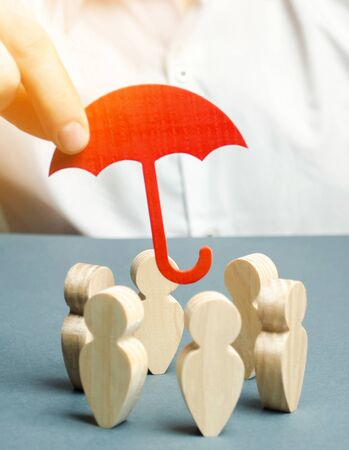 Boss defending his team with a gesture of protection. Life insurance. Customer care, care for employees. Security and safety in a business team. Selective focus