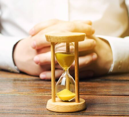 An hourglass and businessman holds his hands in the lock. Job interview concept. Business planning. Management and distribution of time. Making a business deal. Debt restructuring.