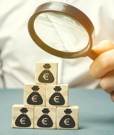 Businessman holds magnifying glass over cubes with euro. Analysis of profits and revenues in the company. Distribution of money. The accumulation of capital. Budget planning. Business concept Stockfoto