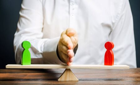 Wooden figures of people on scales and a mediator  arbitrator. Resolving conflict situations and disputes. Conclusions of the peaceful resolution of disputes. Conflict of interest. Business opponents