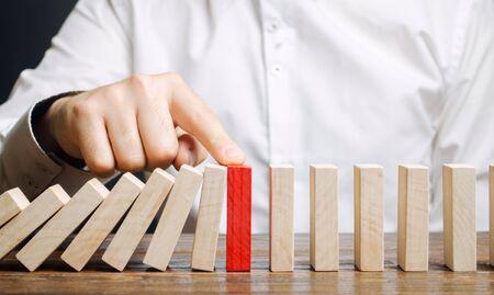 Geschäftsmann stoppt den Dominofall. Risikomanagement-Konzept. Erfolgreiches starkes Geschäft und Problemlösung. Zuverlässiger Führer. Stoppen Sie die destruktiven Prozesse. Strategieentwicklung. Umschuldung Standard-Bild