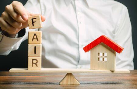 Blocs de bois avec le mot Fair et une maison en bois. Juste valeur de l'immobilier et du logement. Évaluation des biens. Évaluation à domicile. Évaluateur de logement. Accord juridique transparent. Achat/vente d'appartement.