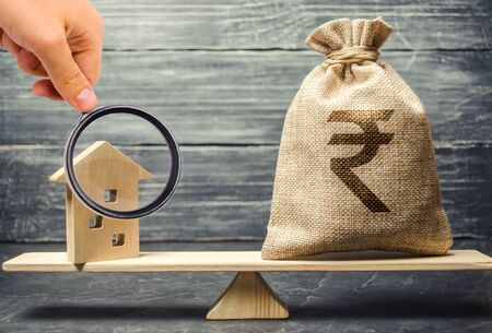 Money bag with indian rupee (rupiah) and wooden house on scales. Fair value of real estate and housing. Payment of the mortgage interest rates. Redemption of taxes. Tax refund. Apartment valuation
