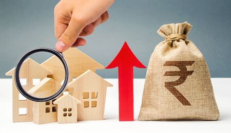 Money bag with arrow up and miniature wooden houses. The concept of rising property prices. High mortgage rates. Expensive rental apartment. Growing demand for home purchase. Indian rupee (rupiah)