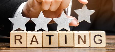 Businessman puts a fourth star above the word Rating on wooden blocks. The concept of the high rating of hotels and restaurants. The evaluation of critics and visitors. Quality level. Four