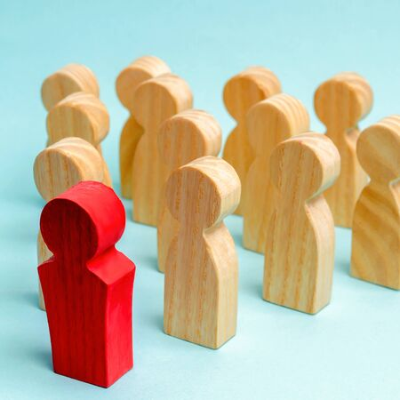 Wooden figures of people. The boss of the business team indicates the direction of movement to the goal. The crowd is following the leader. The concept of leadership and team management. Teamwork. 写真素材