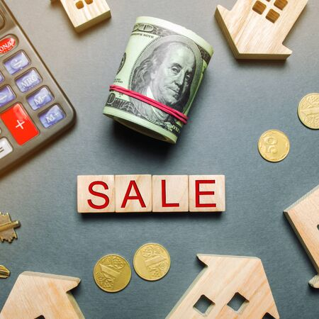 Table with wooden houses, calculator, coins, magnifying glass with the word Sale. Property For Sale. Sell an apartment or house. Housing for sale. Real Estate Agent Services. Realtor