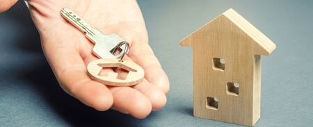 A man holds a trinket key with a house and a wooden home. Real estate concept. Realtor services. Sale of property. Buy housing. Apartments for rent. Mortgage. House for sale. Building construction 写真素材