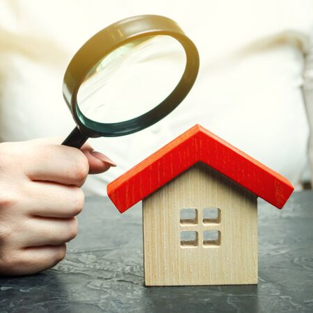 A woman is holding a magnifying glass over a wooden house. Real estate appraiser. Assessment of the condition of the house. Property valuation  appraisal. Search for housing and apartments.