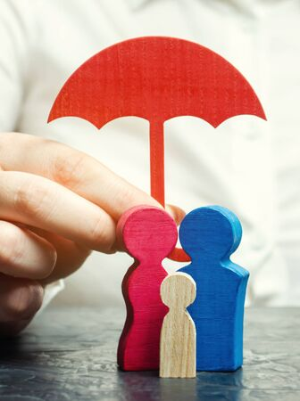 Insurance agent services. Concept of life and health insurance. Social protection of people. Security and support. Miniature wooden figures of people in the form of a family