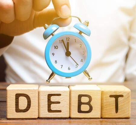 Wooden blocks with the word Debt and the clock in the hands of a businessman. Timely payment of debt. Time to pay off debts. Penalty for late payment and poor credit rating. Business and finance