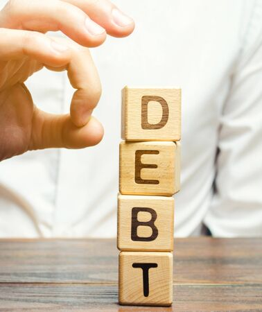 Businessman removes wooden blocks with the word Debt. Reduction or restructuring of debt. Bankruptcy announcement. Refusal to pay debts or loans and invalidate them. Debts service relief 写真素材