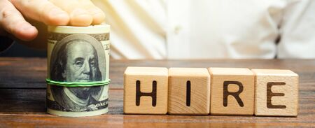 Wooden blocks with the word Hire and dollars. The offer of the salary level at the interview. Raise wages. Transition to a higher paying job to another employer. Career growth and perspective work
