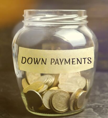Glass jar with the word down payments. Payment used in the context of the purchase of expensive items such as a car and a house, whereby the payment is the initial upfront portion of the total amount 写真素材