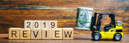Forklift truck carries a bundle of dollars to inscription Review 2019. Audit of business and enterprises, government agencies and services. Annual report and financial performance indicators
