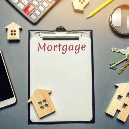 Table with wooden houses, calculator, coins, magnifying glass with the word Mortgage. Buying a home in debt. Purchase a house on credit. Loan on the property. Interest rates calculation. Real estate 写真素材