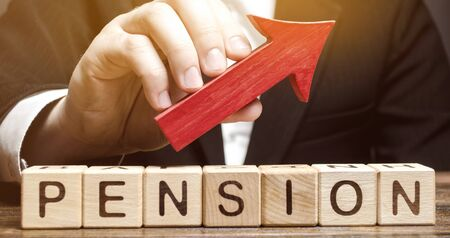 Wooden blocks with the word Pension and up arrow. Improving the financial condition of older people. Surcharge and pension supplements. Loan portfolio growth. Increase pensions fund. Growing payments