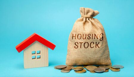A money bag with the word Housing stock and a miniature house. Residential buildings and premises intended for permanent residence of people. Real estate investing. Construction financing concept.