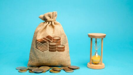 Money bag with coins and a clock  hourglass. Time management and distribution. Concept of saving money. Planning work. Business strategy and investment. Performance and profitability. Savings 写真素材