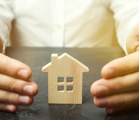 Insurance agent protects the house with a gesture of protection. The concept of property insurance and housing. Security and safety in the home. Real estate