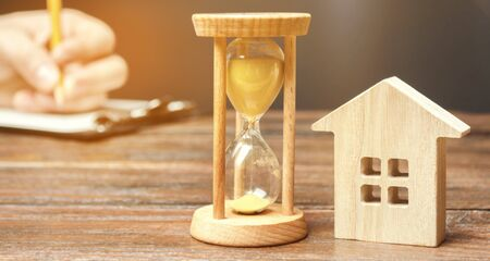 Wooden house and clock. A person signs documents. Signing a contract to rent a house or apartment. Making a will. Testament property. Buying or selling real estate. Mortgage agreement. Leasing