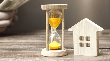Wooden house and clock. Businessman counting money. Payment of deposit or advance payment for renting a home or apartment. Long-term mortgage on the house. Tax and mortgage vacations. Pledge 写真素材