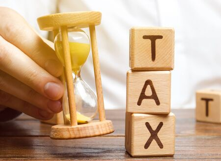 Businessmans hand holding a hourglass near the wooden blocks with the word Tax. Time to pay taxes. The concept of annual taxation. Taxes on vehicles, property, purchases, luxury. State fee