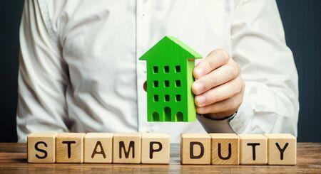 Geschäftsmann und Holzklötze mit dem Wort Stempelpflicht und Haus. Steuern, die bei der Übertragung von Immobilien zwischen zwei Parteien erhoben werden. Kauf von Wohnungen und Grundstücken. Eigentum. Stempelsteuer Grundsteuer / SDLT