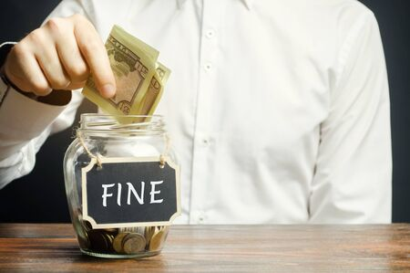 A man puts dollars in a glass jar with the word Fine. Saving money and paying a fine. Punishment for a crime and offense. Financial punishment. Violations of traffic laws. Fraud. Monetary penalty.