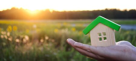 Wooden house in the hands in the sunset background. Real estate concept. Eco friendly home. Symbol of happy family life. Buy a housing outside the city. Search for hotel on vacation. Selective focus