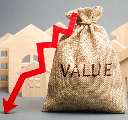 Eine Geldtasche mit dem Wort Wert, Holzhäusern und Pfeil nach unten. Das Konzept der Senkung der Marktpreise von Immobilien. Niedriger Preis für die Anmietung eines Hauses oder einer Wohnung. Reduzierte Miet- und Hypothekenzinsen