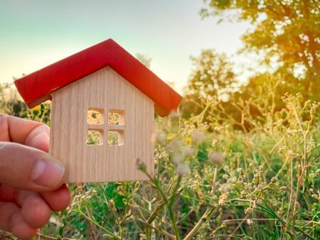 Miniature wooden house in the hands of a man outdoors. Real estate concept. Eco-friendly home. Buying a housing outside the city. The urban downshift. Nature. Fresh air. Mortgage, loan. Red roof Banco de Imagens