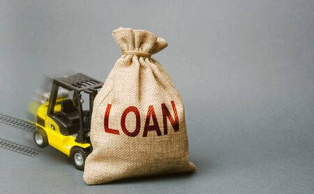 Yellow forklift truck crashed into the bag with the word loan and can not lift it. Inability to repay a loan, debt restructuring. High business load, lack of support. Unprofitable enterprise. penalty 版權商用圖片