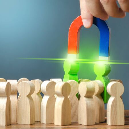 Businessman with a magnet pulls two green figures of people out of the crowd. Formation of a new business team of applicants. Recruiting new workers. Search talented workers with career potential 版權商用圖片