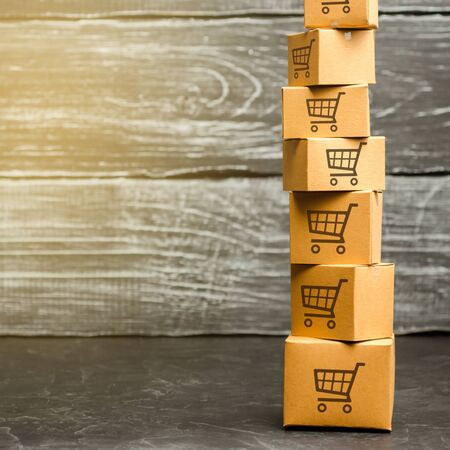 Tower of cardboard boxes with pattern of shopping carts. Purchasing power, delivery order. E-commerce, logistics, distribution. commerce, online shopping. Sales of goods and services. Copy space