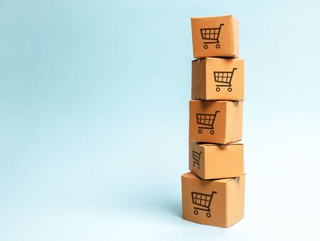 Tower of cardboard boxes with pattern of shopping carts on a blue background. commerce, online shopping. Purchasing power, delivery order. E-commerce, logistics, distribution and sales.