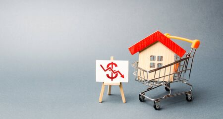 House in the shopping cart and a stand with red chart arrow down. The fall of the real estate market. concept of value or cost decrease. low liquidity and attractiveness. cheap rent or cost of buying.