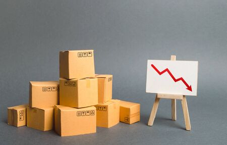 A pile of cardboard boxes and easel with red arrow down. Decrease in the quality, price, quantity and competitiveness of goods and products. Concept drop in industrial production, sales fall. Stockfoto - 128631720