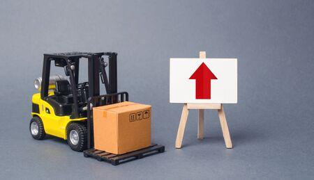Il carrello elevatore giallo porta una scatola accanto a un cavalletto con una freccia rossa verso l'alto. Aumentare il ritmo di produzione di beni e servizi, benessere economico. Esportazioni, importazioni. aumento delle vendite. Alti volumi commerciali Archivio Fotografico