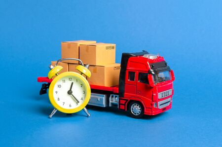 A truck with cargo cardboard boxes and a yellow alarm clock. Express delivery in short time concept. Temporary storage, limited offer and discount. Optimization of delivery logistics Transport company