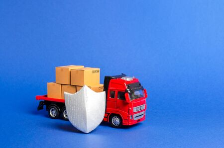 Red truck with a load of boxes behind the shield. Cargo insurance, transportation safety. Guaranteed quality and speed of delivery, security of goods. Transport valuable and dangerous products.