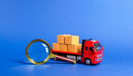 Red truck loaded with boxes and a magnifying glass. Search for a carrier and routes for transportation. Tracking freight. Transit of goods and products. Customs inspection and fees payment. Business