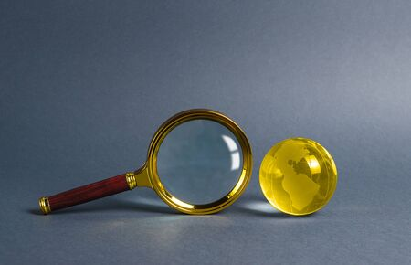 Magnifying glass and planet earth glass ball. Concept of global search and globalization process. International business and logistics. Search engine, exploration of the world. Border transparency. 版權商用圖片
