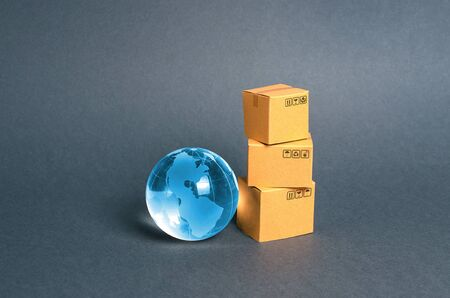 Blue glass planet globe and a stack of cardboard boxes. The concept of commerce and trade, cargo delivery, exchange of goods. Globalization, markets. Business and industry, transport infrastructure.