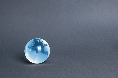 Blue glass planet globe on a gray background. Globalization and markets. Preservation of the environment and reduction of harmful effects on the ecosystem. International diplomacy. Foreign languages. Stock fotó