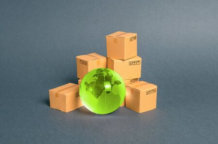 Green glass planet globe and a pile of cardboard boxes. Business and industry, transport infrastructure. The concept of commerce and trade, cargo delivery, exchange of goods. Globalization, markets. 版權商用圖片