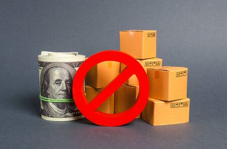 The prohibition sign NO blocks a bundle of dollars money and cardboard boxes. Embargo, trade wars. Restriction on importation goods, proprietary for business. Sanctions and economic restrictions 版權商用圖片