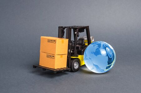 Forklift carrying boxes and blue planet earth glass globe. The concept of commerce and trade, cargo delivery, exchange of goods. Globalization, markets. Business and industry, transport infrastructure